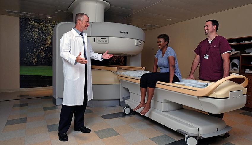 a patient sitting on an open mri machine talking to the radiologist