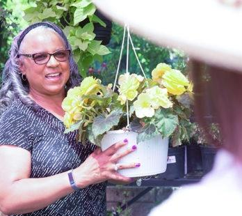 A woman who is picking out a plant at the nursery
