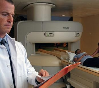 a doctor standing in front of a true open mri machine