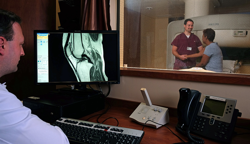 technician explaining the open sided mri to a patient